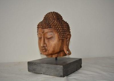 Houten sculptuur, hoofd van Boeddha. op een blauwe steen sokkel. Het hoofd is 22 cm hoog